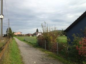 Areal Gatterächer Ost: Noch unerschlossenes Bauland, das teilweise der Einwohnergemeinde gehört. Im Vordergrund rechts die Kindergärten Gatterächer, links die Bahnlinie Würenlos - Otelfingen.